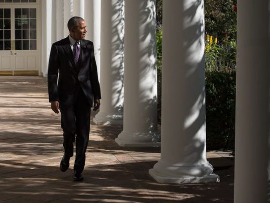 President Obama walks down the colonnade at the White