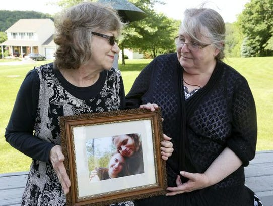 Lyn Coleman and Linda Boyle hold a picture of their
