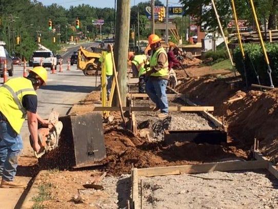 A work crew constructs a sidewalk on Hendersonville