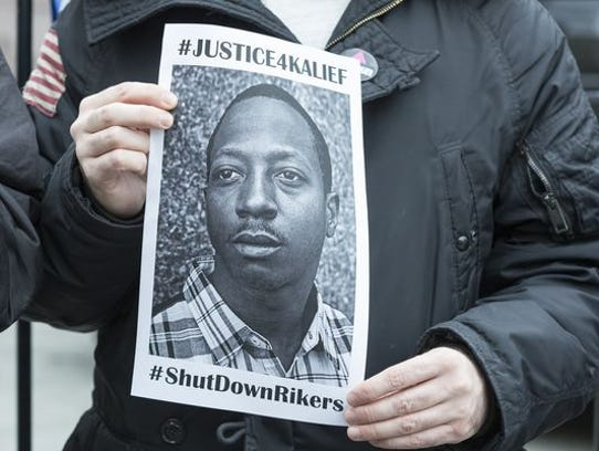 A demonstrator holds a picture of Kalief Browder during