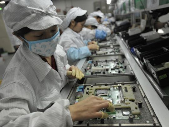 Workers assemble electronic products at a Foxconnn