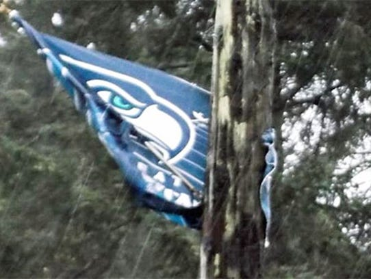 A Seahawks flag flaps in the wind and rain in Seattle.