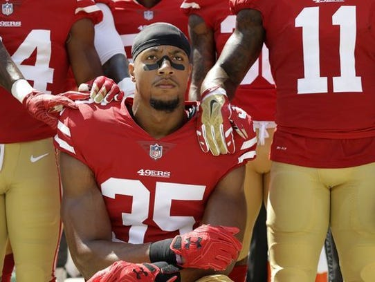Eric Reid of the San Francisco 49ers takes a knee during