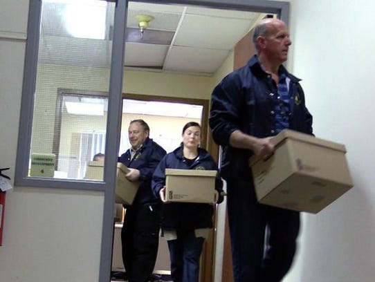 Detectives carry documents from Spring Valley offices