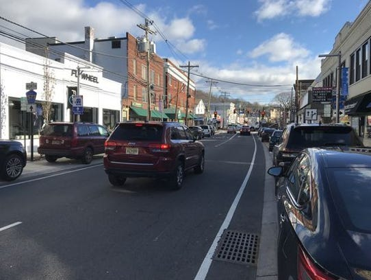 A vehicle drives down Millburn Avenue, where raised parking spaces have been installed as part of a controversial streetscape project.