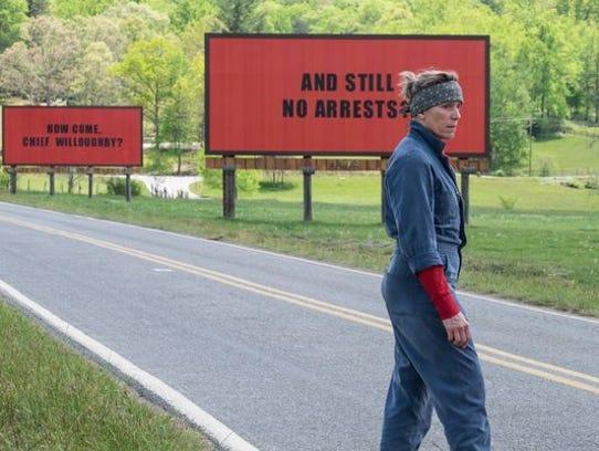Actress Frances McDormand walks in front of the billboards