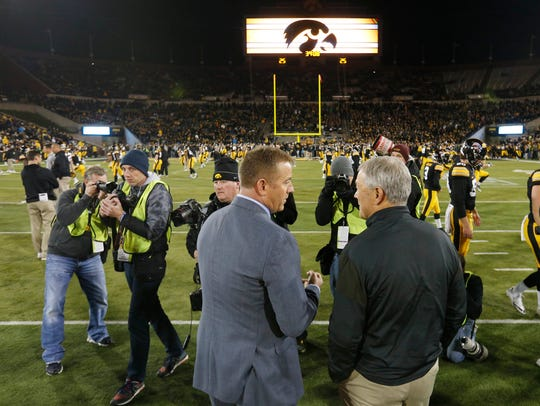 Iowa head coach Kirk Ferentz talks with sports commentator
