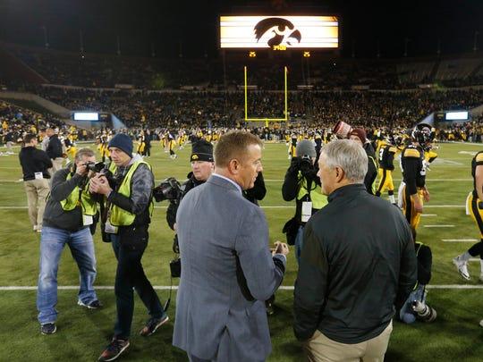 Iowa head coach Kirk Ferentz talks with sports commentator Kirk Herbstreit Saturday, Nov. 12, 2016, before their game against Michigan at Kinnick Stadium in Iowa City.
