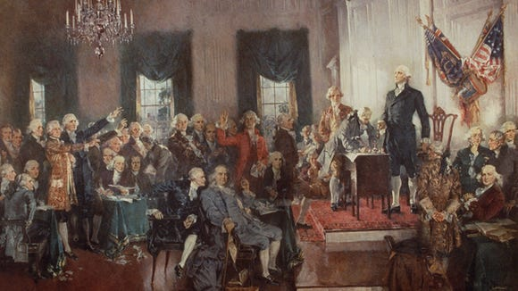 """Delegates at the Constitutional Convention in 1787 prepare to sign the U.S. Constitution in the painting """"Scene at the Signing of the Constitution of the United States"""" by artist Howard Chandler Christy."""