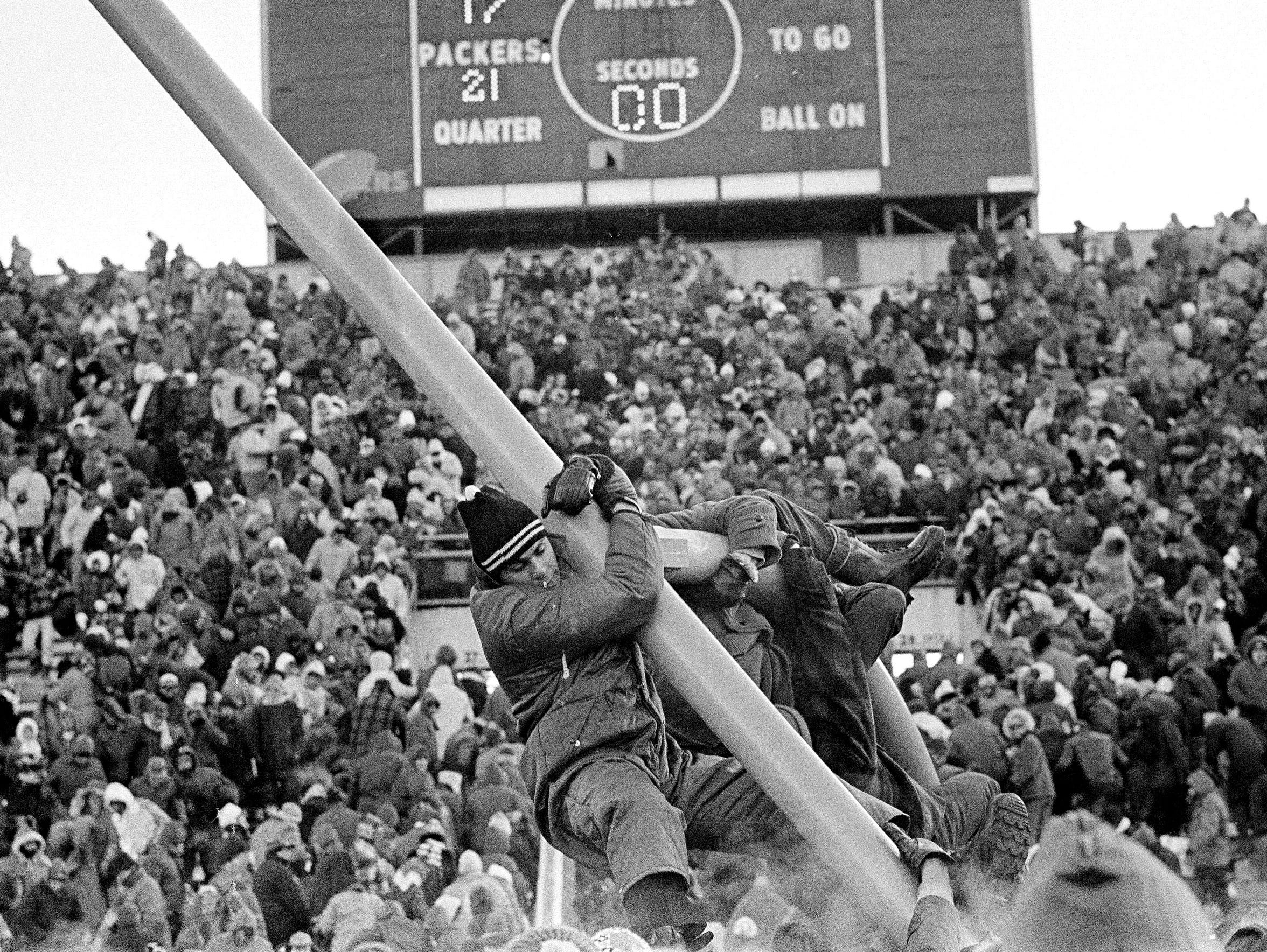 Fans climb on the goal post at Lambeau Field after the Green Bay Packers beat the Dallas Cowboys, 21-17, in the 1967 NFL Championship Game, better known as the Ice Bowl.