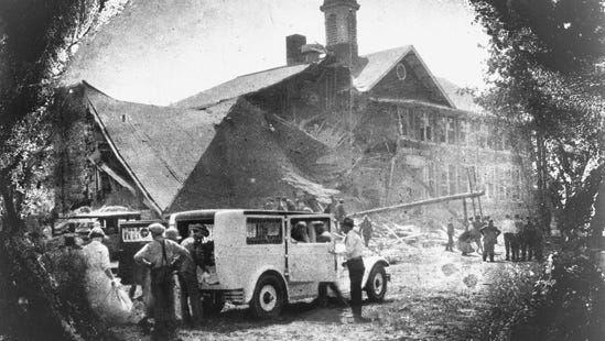 Loading an ambulance in the shadow of destruction, May 18, 1927.