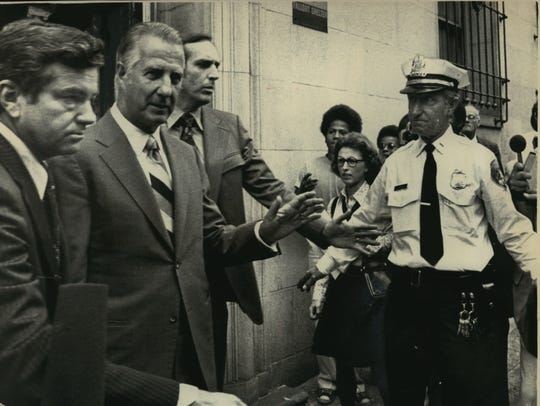 Flanked by Secret Service agents, Spiro Agnew leaves