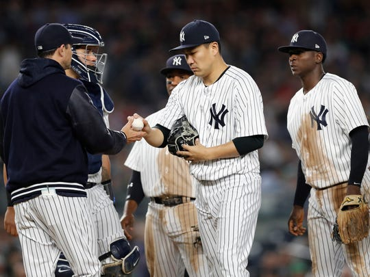 New York Yankees starting pitcher Masahiro Tanaka hands the ball to manager Aaron Boone, left, during the sixth inning of the team's baseball game against the Boston Red Sox in New York, Wednesday, May 9, 2018.