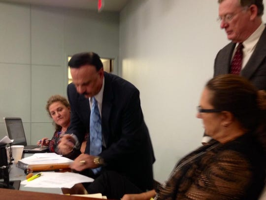Don DeDonatis, chairman and chief executive officer of the U.S. Specialty Sports Association, signs the deal with Brevard County related to Space Coast Stadium after it was approved at Thursday night's County Commission meeting. Looking on are County Attorney Scott Knox and staff of the clerk to the board.