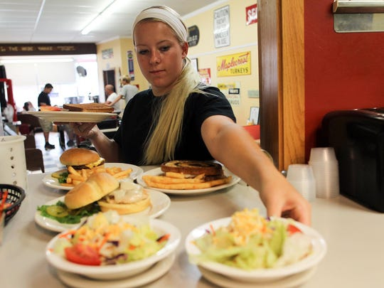 Chelsea Kral picks up an order for a table at Mr. O's Cafe in Wellman on Friday.