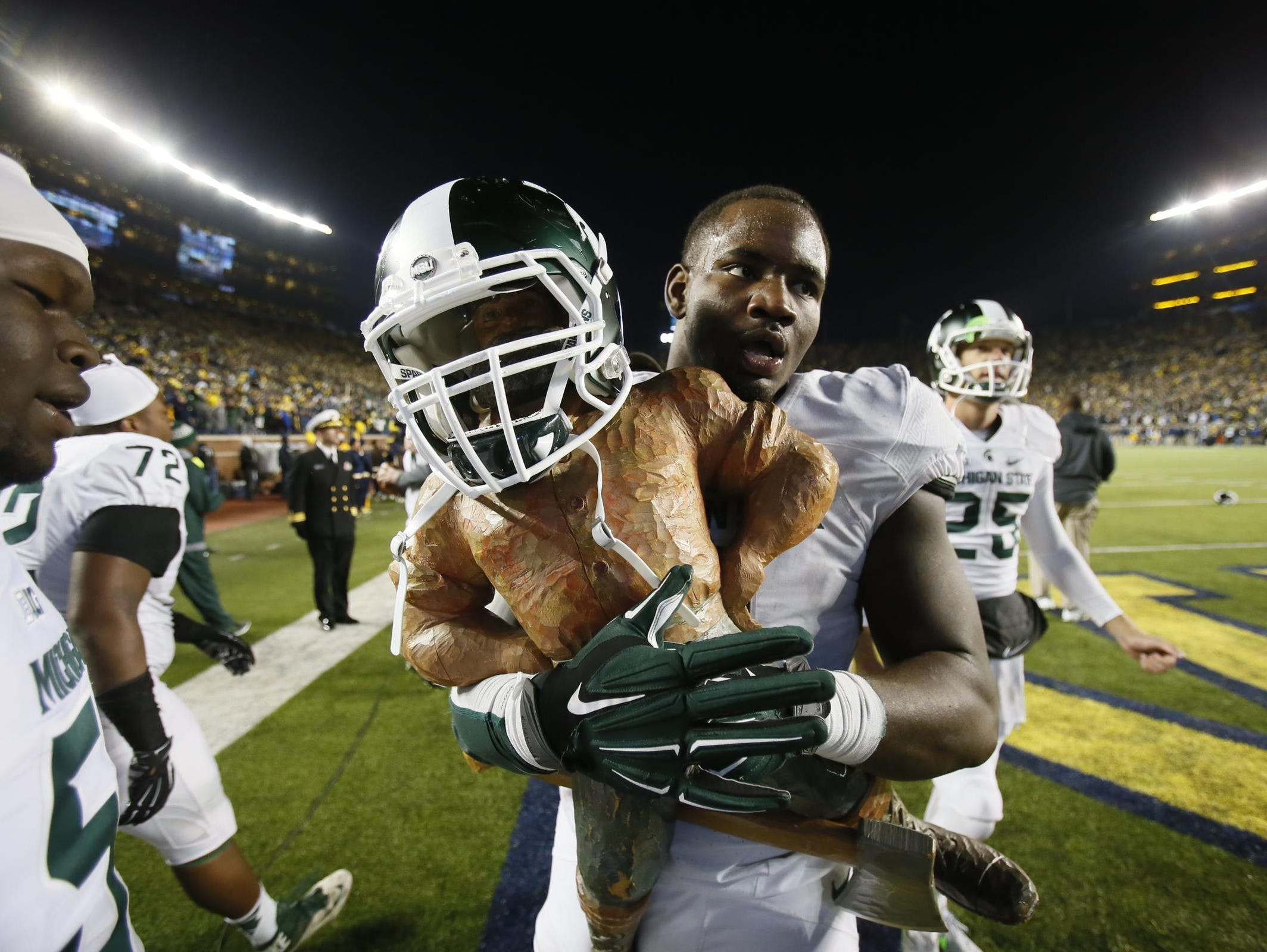 Michigan State's Lawrence Thomas carries the Paul Bunyan trophy after the Spartans' final-play 27-23 victory over U-M on Oct. 17 in Ann Arbor. Thomas was the top-ranked prospect in the state out of high school.