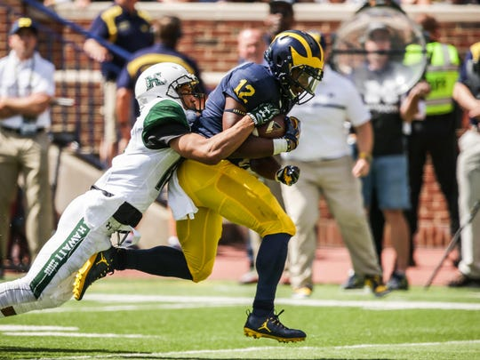 U-M's Chris Evans is tackled by Hawaii's Jalen Rogers on Sept. 3. Evans has 157 yards in 21 carries.