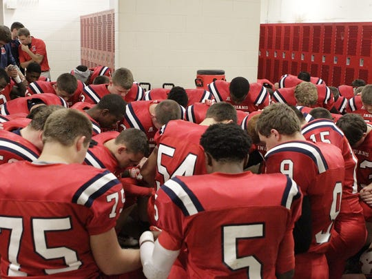 The Norwood Indians kneel for a word of prayer before their Oct. 17 game with Williamsburg.