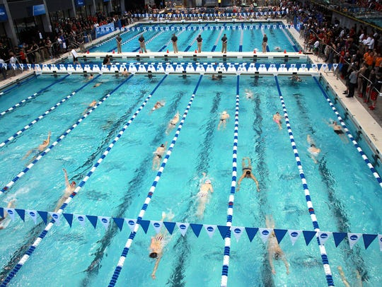 Swimmers warm up in the practice pool at the NCAA swimming