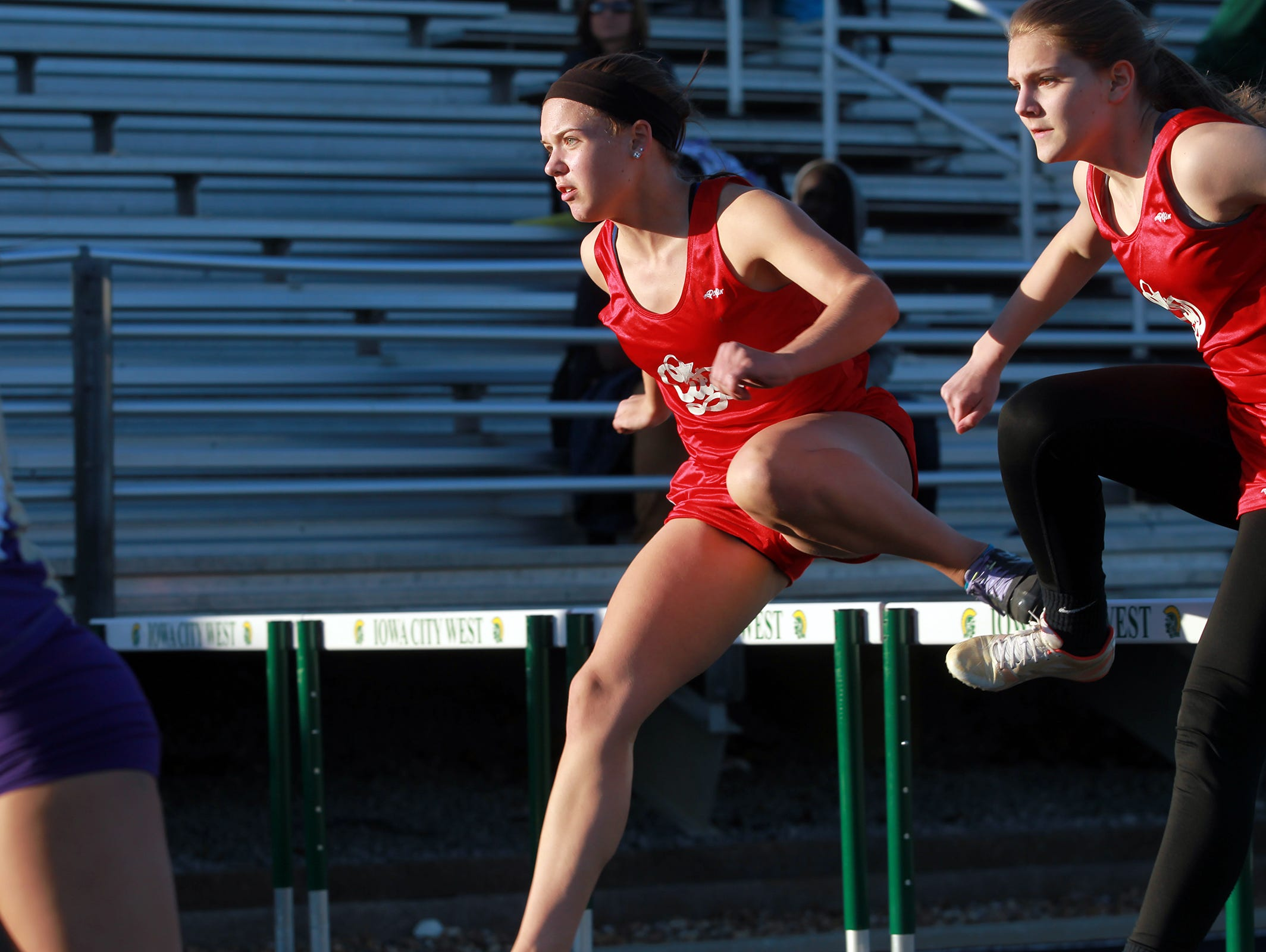 City High's Elke Windschitl, left, and Anna Roemerman compete in the 100 meter hurdles at the Women of Troy Relays at West High on Tuesday, March 31, 2015. David Scrivner / Iowa City Press-Citizen