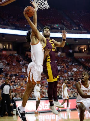Central Michigan guard Matt Beachler (22) drives to the basket against Texas forward Jericho Sims (20) during the first half of an NCAA college basketball game, Saturday, Dec. 14, 2019, in Austin, Texas. (AP Photo/Eric Gay)