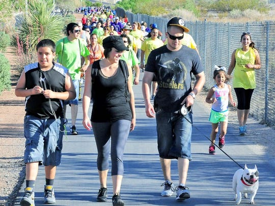Walking along Triviz Drive, from left to right, Andres Mendoza, 11, Brenda Beltran, Anthony Rauch, and French bulldog Kudo participate in the 2013 March of Dimes annual March for Babies.