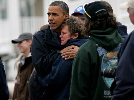 President Obama comforts Donna Vanzant, owner of the North Point Marina on East Shore Dr. in Bergentine on Oct. 31, 2012. Boats from the marina ended up in the street after Hurricane Sandy hit New Jersey.