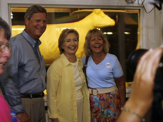 Sen. Hillary Clinton, center, stands with former Iowa Governor Tom Vilsack and Christie Vilsack in front of the butter cow at the Iowa State Fair.