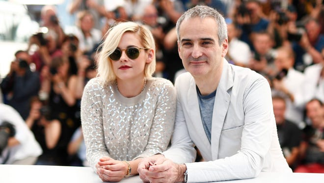 Kristen Stewart (L) and French director Olivier Assayas (R) pose during the photocall for 'Personal Shopper' at the 69th annual Cannes Film Festival.