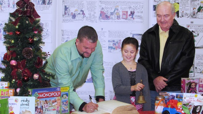 Doug Haskins, Arctic League board member, signs the Big Book last year at Arctic League headquarters. Looking on are Riley Fesetch, the 2015 bell ringer, and Haskins' father Bob Haskins, Arctic League board president.