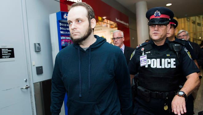 Joshua Boyle, left, gets a police escort after speaking to the media after arriving at the airport in Toronto