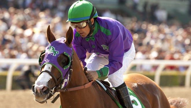 In a photo provided by Benoit Photo, California Chrome and jockey Victor Espinoza win the Santa Anita Derby horse race Saturday at Santa Anita in Arcadia, Calif.
