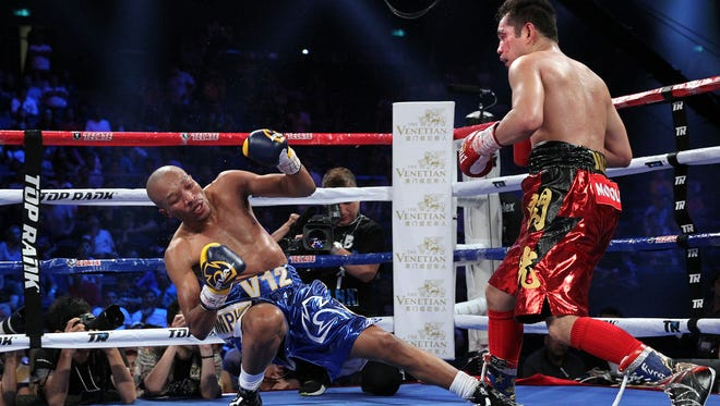 Nonito Donaire knocks down Simpiwe  Vetyeka in the 4th round enroute to winning a 5th round technical decision in Macau.