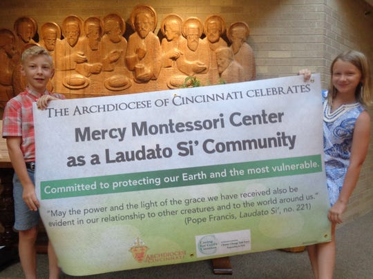 Mercy Montessori students Rachel Losch and Reece Flaspohler proudly display the Laudato Si' Banner they received on behalf of their school during a recognition service June 18 at Community of the Good Shepherd in Symmes Township.