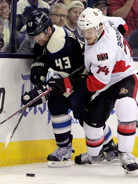 Ottawa Senators' Mark Borowiecki, right, and Columbus Blue Jackets' Scott Hartnell fight for a loose puck during the second period of an NHL hockey game Tuesday, Oct. 28, 2014, in Columbus, Ohio. (AP Photo/Jay LaPrete)
