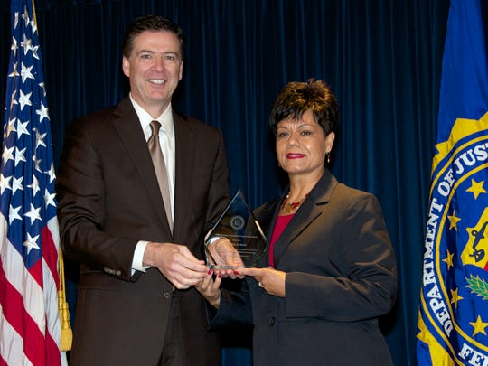 FBI Director James Comey presents a 2013 Director's Community Leadership Award to El Paso Independent School District counselor Patricia Scott for helping the agency uncover corruption in the district.