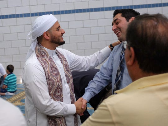 Imam Shaykh Mohamed Almasmari (center) talks with worshippers following prayer at the Muslim Unity Center mosque in Bloomfield Hills on Friday June 3, 2016.