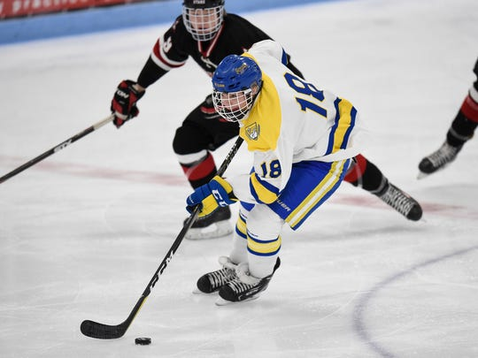 Cathedral's Mack Motzko skates with the puck during