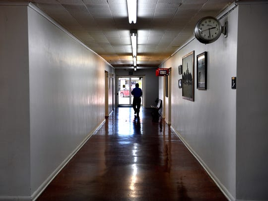 A figure walks toward the exit at the Coleman County Courthouse on Wednesday. The interior retains the same design touches added when it was modernized in 1952.