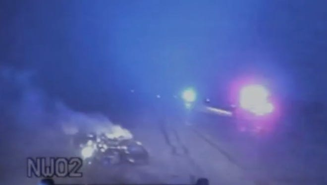 This still photo from a law enforcement officer's dash cam shows the aftermath of a fatal high-speed chase that left Carl Albert Stamm IV dead in 2011. In the lower left corner is Stamm's motorcycle, which struck a Fowlerville police officer's cruiser.