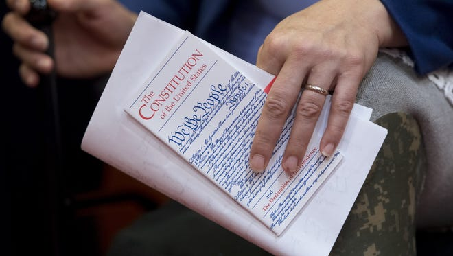 A member of Congress holds a pocket U.S. Constitution.