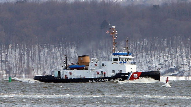 A U.S. Coast Guard icebreaker passes by as U.S. Sen. Charles Schumer talks at the Haverstraw Ferry terminal on Thursday. Schumer wants the Coast Guard vessel to make more frequent trips in the area to break up the ice.