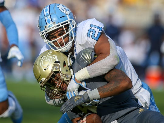 Oct 5, 2019; Atlanta, GA, USA; North Carolina Tar Heels linebacker Chazz Surratt (21) tackles Georgia Tech Yellow Jackets quarterback James Graham (4) in the first half at Bobby Dodd Stadium. Mandatory Credit: Brett Davis-USA TODAY Sports