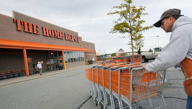 FILE - In this file photo made Oct. 6, 2009, employee John Abou Nasr pushes shopping carts in the parking lot of a Home Depot in Methuen, Mass. Home Depot's data breach could wind up being among the largest ever for a retailer, but that may not matter to its millions of customers.