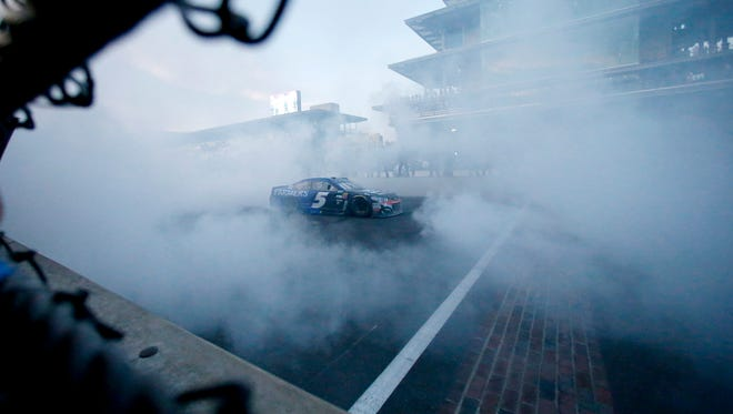 Kasey Kahne (5) does a burn out on the main straight after winning the NASCAR Brickyard 400 auto race at Indianapolis Motor Speedway Sunday.