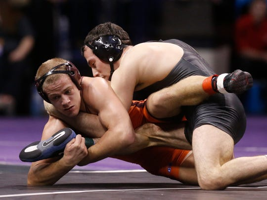 Virginia Tech's Devin Carter, left, who will be a speaker at the Fishburne wrestling camp in June, wrestles North Carolina's Evan Henderson in the 141-pound semifinals at the 2014 NCAA Division I wrestling championships in Oklahoma City.