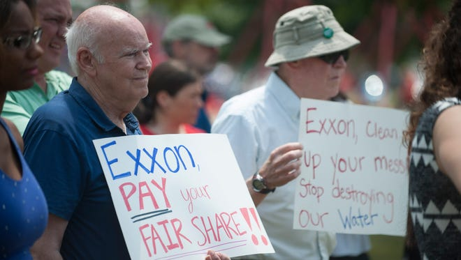 Fred Fall of Cherry Hill and Mike Delozier of Deptford holds up signs as concerned citizens and environmental leaders join together to oppose the Exxon Settlement agreement during a protest at Ft. Billings Park in Paulsboro Thursday.