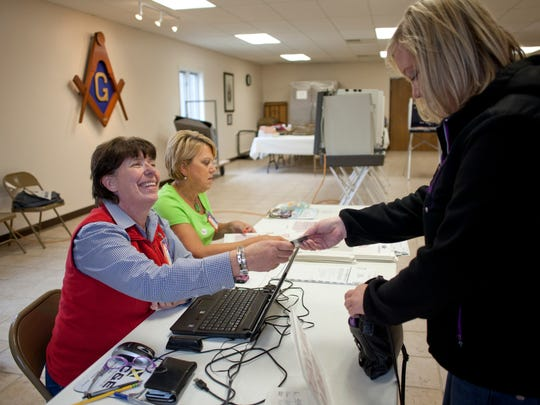 Election official Lucie DeLine checks Sara Matthew's identification as she prepares to vote Tuesday, May 5, 2015 in Precinct One at the Masonic Temple in Marysville.