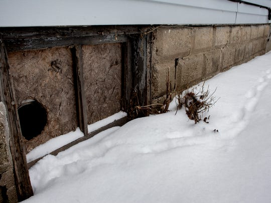 Animal tracks lead through the snow to a hole in a boarded window at 230 13th Street in Port Huron. The house is one of many that will be demolished as part of a grant from the Michigan State Housing Development Authority.