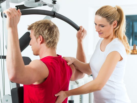 A woman helping a man during physiotherapy